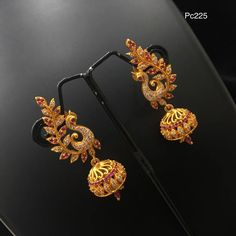 BEautiful jumkhis with dancing peacock design. Jumkhi studded with white and pink color CZs. Gold Jhumka Earrings, Indian Jewelry Earrings, Jewelry Design Earrings, Gold Earrings Designs, Gold Jewellery Design, Ear Jewelry, Antique Earrings, Necklace Designs, Beaded Jewelry