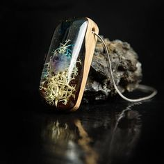 A miniature underwater world in a unique wood and resin pendant, made from recycled stabilized wood, amethyst chips, moss and transparent epoxy resin. The pendant was created with great care to detail and has a glossy finish. Dimensions: Max length 4 cm (1.57) Max Width 1.6 cm (0.62) Max