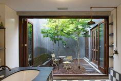 Incredible courtyard with trees and gravel and CLASS. Design by Franchesca Watson, found via Desire to Inspire
