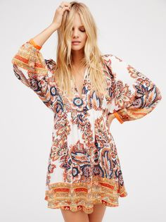 Say You Love Me Mini Dress | In a babydoll-inspired silhouette and silky fabric this retro printed mini dress features a long V-neck and pleat detailing around the waist. With wide long sleeves and removable slip with adjustable straps.