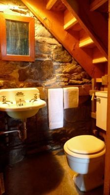 Nice powder room under the stairs with stone wall and wall mounted sink.