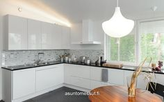 Keittiö asuntomessutalossa: tumma työtaso, vaaleat yläkaapit yhdellä seinällä, valkoinen liesituuletin