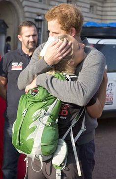 Prince Harry hugs wounded vet Kirstie Ennis as she ends her 1000 mile Walk with the Wounded at Buckingham Palace