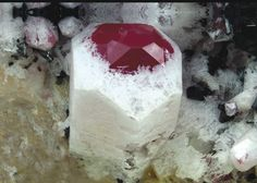 Minerals in a Granitic Pegmatite: Red Beryl with Albite microcrystals taking advantage of the corroded crystal surface
