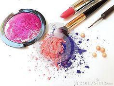Makeup brush and crushed eyeshadows on white background