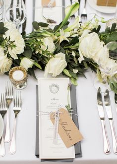 Dining tables were decorated with ivory roses accented with greenery, with…