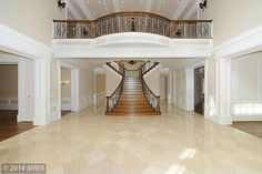 Traditional Staircase with Crown molding, High ceiling, Hardwood floors, Wrought iron railing, Polished travertine floor