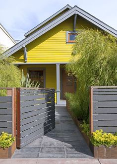 Grey horizontal fence and gate in front of a modern yellow cottage