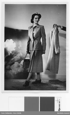 1949-1953. Modell i ylledräkt, hatt, handväska och snörskor, går på stenplattor. En hand sträcker fram en kappa. Bild av moln i bakgrunden. Fotograf: Sten Didrik Bellander