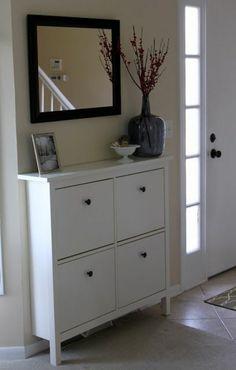 Meuble couloir de couleur blanche, un miroir, une photo et une vase grise.