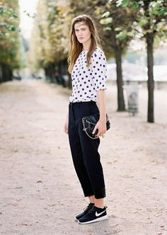 A polka dot t-shirt is tucked into black pants and worn with a black bag and Nike sneakers