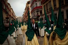 """A man helping to organise the event speaks with a nazareno (hooded penitent) from the """"La Pollinica"""" (The Little Donkey) brotherhood. Semana Santa (Holy Week), 2013. Málaga, Spain. (Jon Nazca/Reuters)"""