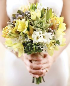 Bouquet of hydrangeas, freesia, alstroemeria, craspedia, leucadendron, mini cymbidium orchids, brunia berries, succulents, parrot tulips, and dusty miller by Tulip