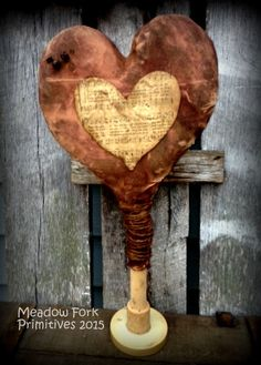 A wonderfully grungy primitive heart mounted on an old spindle. The heart is made from muslin which was stained and painted, sanded, and grungied