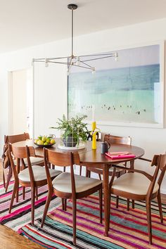 Stylist Emily Henderson used two bright patterned rugs and a large piece of art to bring color into an otherwise neutral dining room.