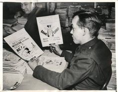 1942- Soldier admires drawings on Christmas V Mail being sent to America from U.S. troops stationed in England.