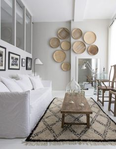Chic African baskets on the wall, patterned rug and earth tones for modern living room