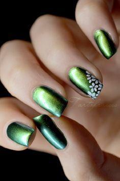 Green and black Ombre nail art. Give a mysterious tint to your nails by adding glitters and flora details on top using white nail polish.