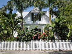 Key West cottages are often surrounded by lathe-turned picket fences that wrap around the entire structure. Blooming bushes add a visual pop and fresh contrast to fancifully painted homes.