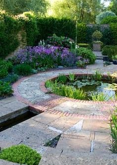 Walled garden built in 1999 to the design of the late Graham Hopewell featuring a circular pond fed by water feature and stepped rill.