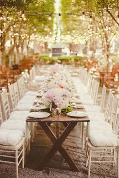 outdoor wedding table with white and pink low centerpieces, white reception chairs and hanging edison lights