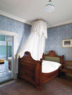 I Prinsflygeln på Stjernsund har alla gästrum stiliga Karl Johansängar med sänghimlar i olika former. Denna säng har svärtade knoppar och lunettdekor på gavlarna.