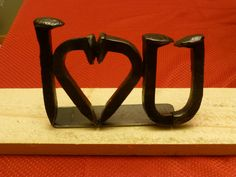 Hand forge from railroad spike, railroad anchor and a piece of pipe.  The I Love You art is individually hand-crafted by our metal artist right here