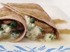 Ricotta Spinach Tacos (makes 2)    1/3 cup ricotta at room temperature   2 tbsp chopped fresh cilantro   1 clove of garlic, chopped   Salt to taste   1 tbsp olive oil (for frying pan)   1/4 of a white onion, sliced into 1/2-inch-thick rings   1/2 cup white mushrooms, sliced   1 1/2 tbsp diced green chile peppers, drained (I used Trader Joe's Fire Roasted Diced Green Chiles)   3 1/2 cups fresh spinach, stemmed   1 tsp ground cumin   2 small whole wheat flour tortillas   Salsa verde