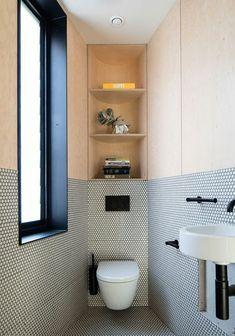 espace aménagé en longueur, modele de salle de bain, idée carrelage salle de bain, mur bicolores, en couleur pêche et en mosaïque en noir et blanc aux motifs graphiques, meuble wc suspendu, étagères type niches, grande fenêtre avec cadre en noir