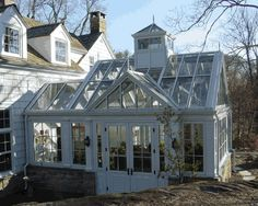 Very nice looking greenhouse attached to a home and designed to nicely blend in with the style and shape of the home.