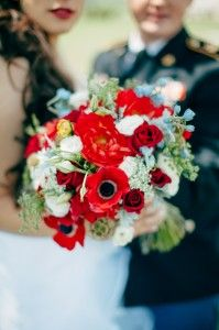 Beautiful rustic bridal bouquet. Red dahlias, red anemonies, red roses, light blue delphinium, white lisanthus, white queen annes lace.  wedding bouquet.