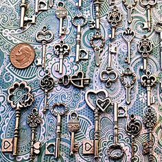 Great variety set of vintage / antique skeleton look key charms!  Flower, heart and other themes! Perfect for crafts, scrap-booking, jewelry, wedding tags or place settings, collections, display - the uses are limited on by your imagination. Various sizes from 3/4 to 2 & 1/2 tall! Made of metal. Most keys are double-sided, but a few, mostly the smaller ones, are flat-backed.  Keep in mind these are reproductions, not actual working keys!  Custom sets available upon request....