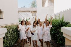 Bridal party popping champagne in robes, fun bridal party photo ideas