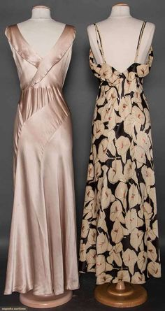 TWO SILK EVENING GOWNS, 1930s (back views) 1 bias cut champagne charmeuse, low cowl neck, grass green waist panel, green & rhinestone buckle; 1 black satin w/ white calla lily print, spaghetti straps & low back