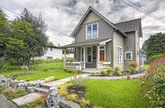 Check out this beautiful, quaint Karina cottage in Washington state. Outside, you'll notice a mixture of grey sidings and a burnt orange door on a covered front porch. The house sits on a lus…