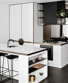 Minimalist white kitchen with black accents and clean lines.