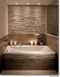 Bathroom stone wall and tile around the tub i'd probably take baths in this tub!