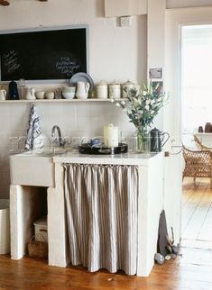 Butler style kitchen sink set in a concrete unit with white tiled worktop and striped curtain