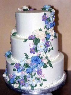 Wedding cake cascading blue purple buttercream flowers.