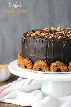 Sinful Samoa Cake. Dark chocolate cake layered with caramel cream cheese. Frosted with a fudgy dark chocolate buttercream and topped with toasted coconut, caramel and cream cheese.