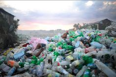 """Cite Soleil"" - A child plays and sleeps in a pile of plastic bottles the community has collectively gathered to sell: April 15, 2011 in Trutier, Cite Soleil, Port au Prince, Haiti. 