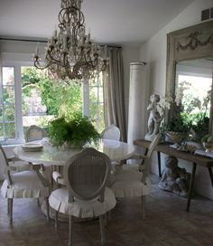 Pretty, neutral dining room. Love the mirror, the dining chairs, and the fabulous chandelier!