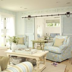 The living room beckons with subtle blue stripes on the walls and a sitting area arranged around the fireplace, which is surrounded with a facade of smooth, round rocks like those found on the local beaches.