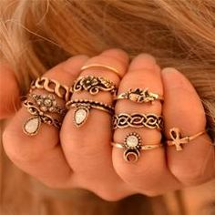 10 piece ring set comes in assorted sizes for midis, pinkies, and all of your fingers! Some rings have iridescent white stones, some are floral and geometric and some have an ankh, an elephant and a c