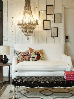 A beaded chandelier hung above a white settee and a black tufted ottoman. Jayson Home & Garden, June/July 2010