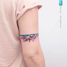 Tatuagem criada por KORAY KARAGÖZLER da Turquia. Elefante nadando em mar de flores no braço.
