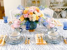 Floral May Day tablescape #flowers #springflowers #tablescape #springtablescape #springdecor #springdesign #springhometour #tablesetting #homedesign #delphinium #roses #hydrangea #floralarrangement