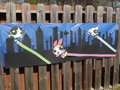 DIY powerpuff girl banner. Four black sheets of large paper cut into the sky line, blue table cloth, printed up the girls off the computer and stuck streamers behind them for their power streaks. It now is being used as a wall poster.