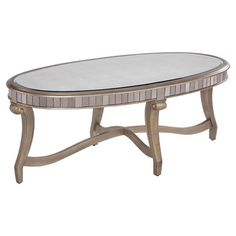 Display a stack of fashion books or perch a hot cup of java atop this lovely coffee table, featuring an oval design and antiqued mirror panels for a gleaming...