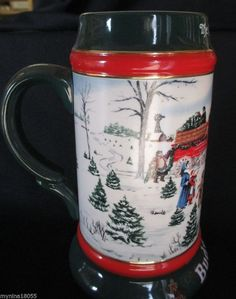 """CS133 - 1991 """" The Season's Best """" Holiday stein. This 7"""" stein was made in Brazil by Ceramarte. Artist Susan Sampson's 2nd in a series of 3 steins. The Clydesdales eight-horse is seen stopping at a tree farm on a cold winter's day. Scene is framed by red and dark green accents and trimmed in gold."""
